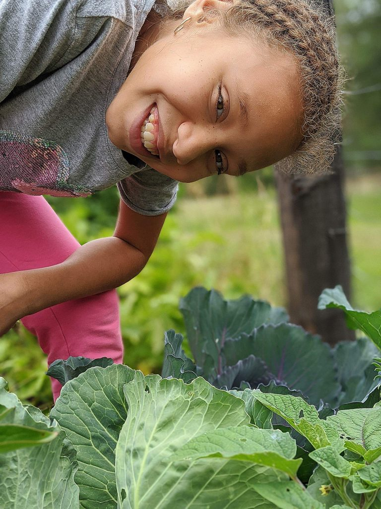 A young Sierra Gardens participant shows off her harvest.