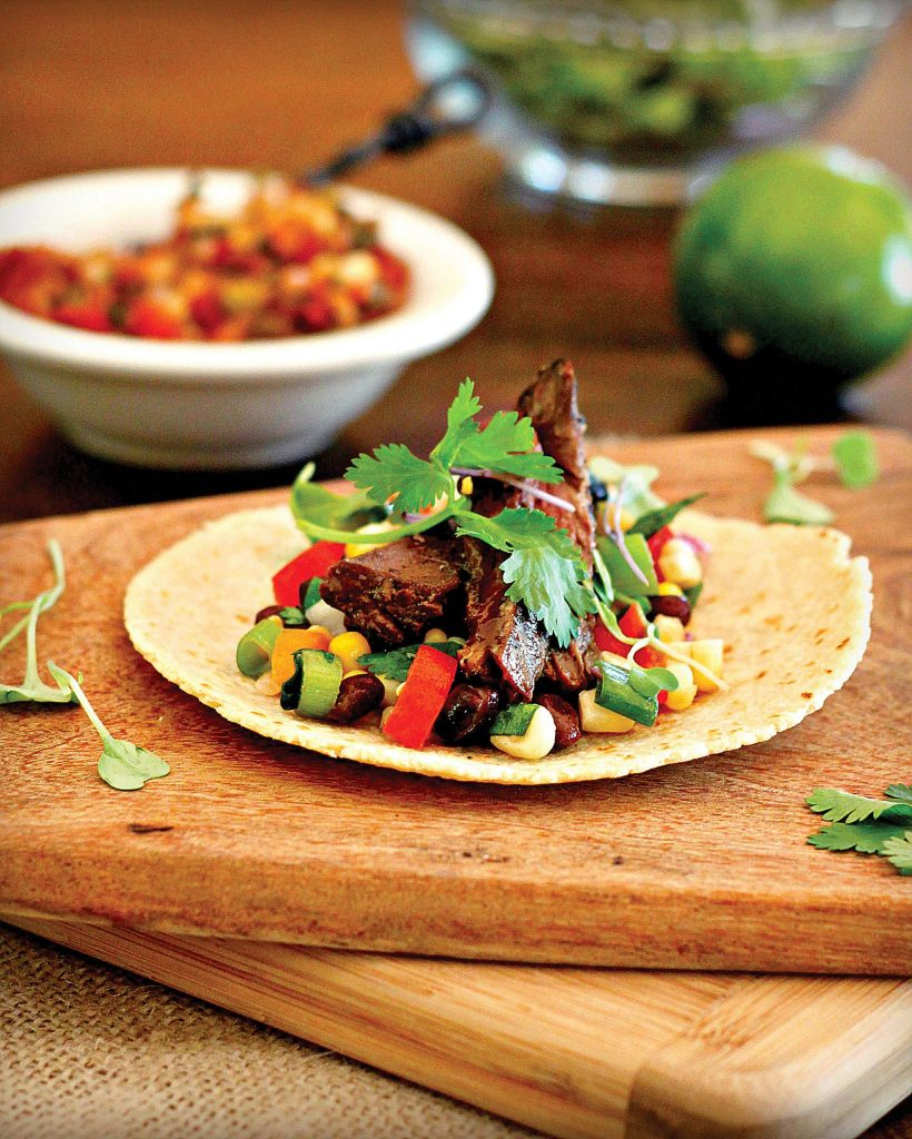 Fajitas are traditionally made with grilled meat, often skirt steak, or chicken and sauteed peppers and onions. The ingredients are presented deconstructed, ready for assembly in soft flour tortillas. Tacos traditionally include ground meat, lettuce, tomato and cheese assembled in a fried corn tortilla.