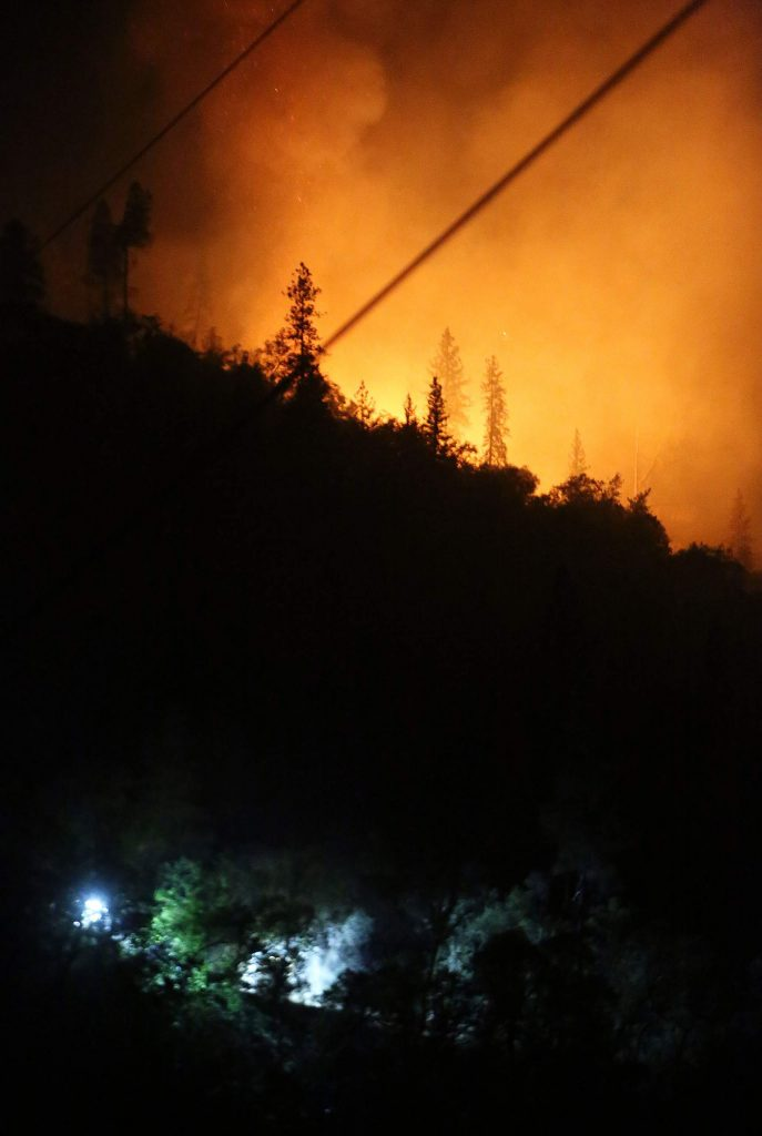 A flank of the Jones Fire illuminates the night sky Tuesday while a pair of bulldozers make fire lines in the night near the Independence Trail.