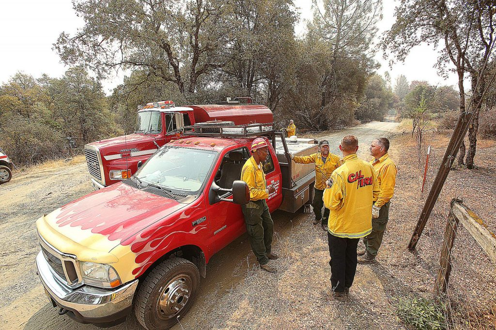 Firefighters fill up on water as they continue to put out hotspots and patrol the Newtown area of Nevada County where the Jones Fire burned.