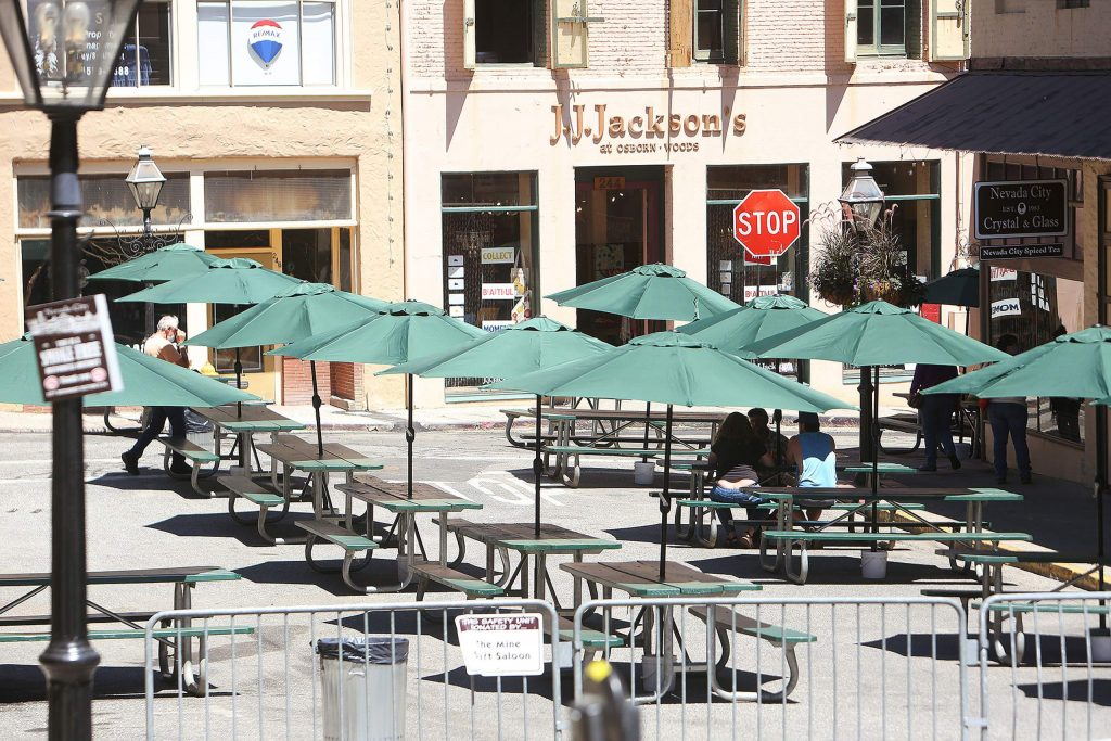 Picnic tables and umbrellas sit on a portion of Pine Street, between Broad and Commercial streets.