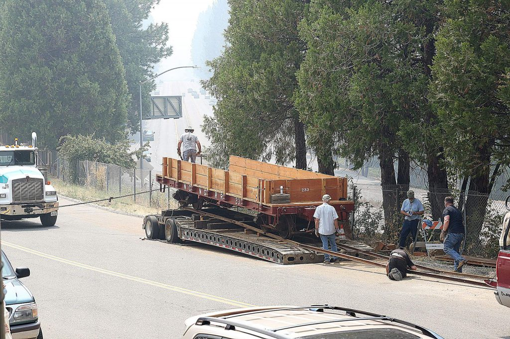 A Robinson Enterprises truck lowers a restored narrow gauge railcar from its trailer onto the section of display track bordering Railroad Avenue in Nevada City.