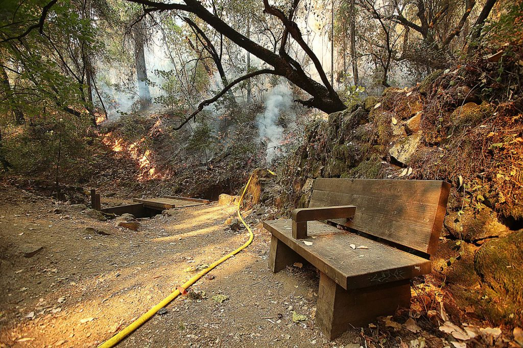 Flames from the Jones Fire burn near a bench along the Independence Trail, which will require a lot of work to rebuild.