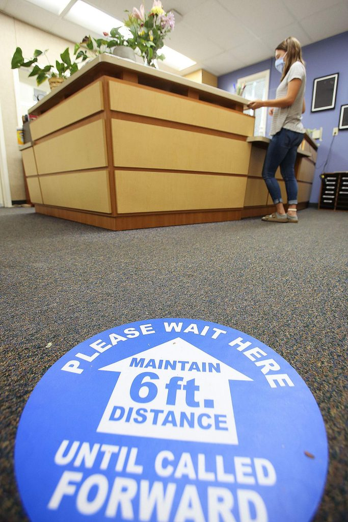 A sign placed on the floor of the Deer Creek Elementary School office asks people to wait before entering. Deer Creek was one of the schools to open for in class instruction earlier last month.