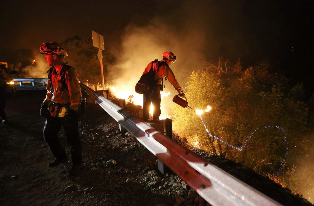 Cal Fire firefighters initiate a firing procedure to back burn fire fuel to the lines of the Jones Fire Tuesday morning along Highway 49.