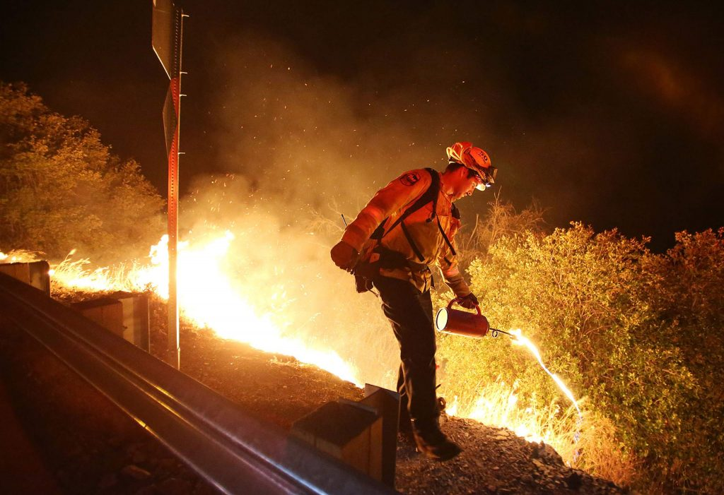 A Cal Fire firefighter initiates a firing procedure where fire fuel is ignited to back burn vegetation down the Yuba River Canyon toward the flames of the Jones Fire Tuesday morning.