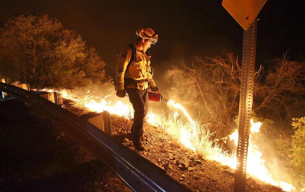 A Cal Fire firefighter initiates a firing procedure where fire fuel is ignited to burn vegetation down the Yuba River Canyon toward the flames of the Jones Fire Tuesday morning.