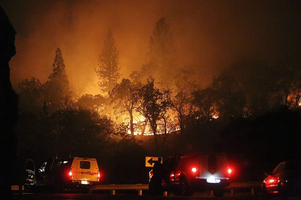 Cal Fire firefighters keep an eye on a firing procedure commencing on the ridge across from Rush Creek and Highway 49.