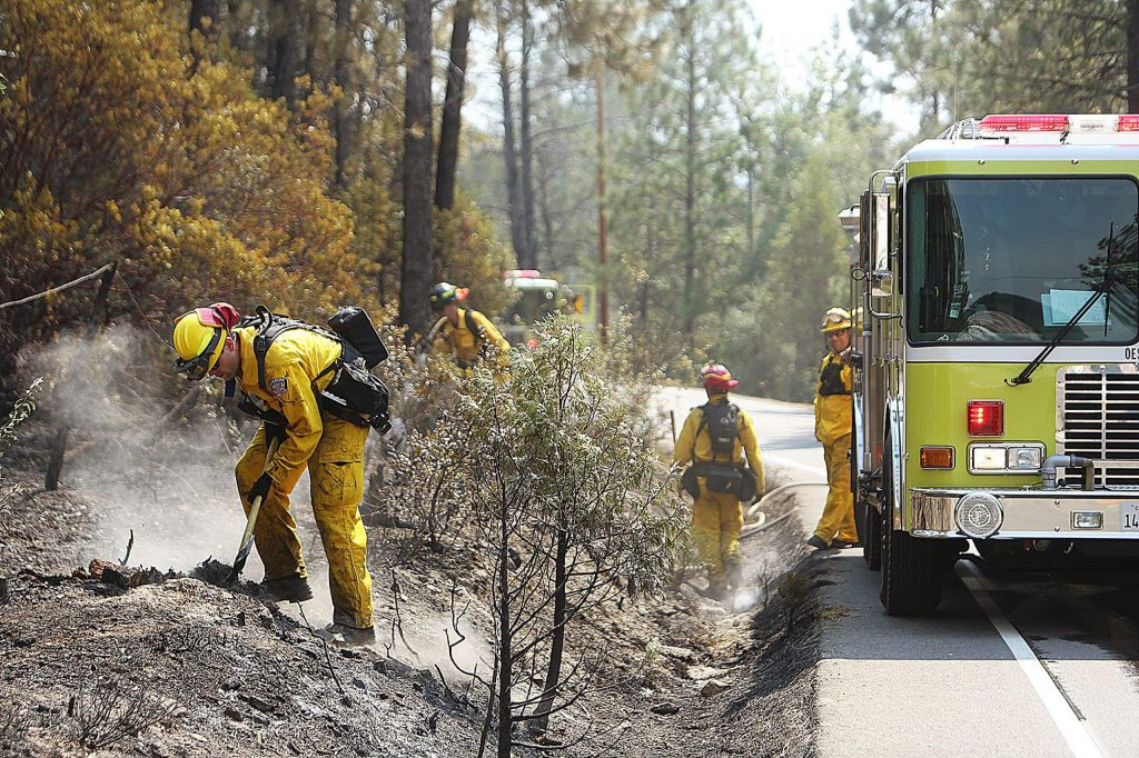 An engine of California Office of Emergency Services firefighters mop up smoldering spots along Newtown Road Tuesday morning.