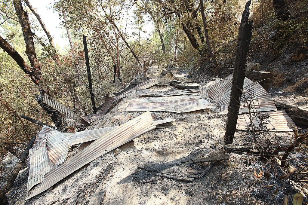 The skeletal remains of the South Yuba River overlook along the Independence Trail sits in a pile of ashes and rubble after the Jones Fire burned through earlier this week. Much of the wooden structures along the trail have burned.