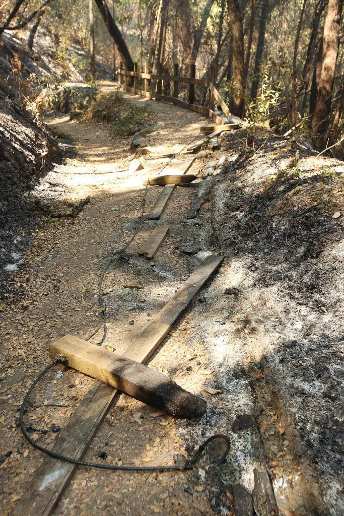 Remnants of a portion of railing sit along the Independence Trail after the Jones Fire burned through earlier this week.