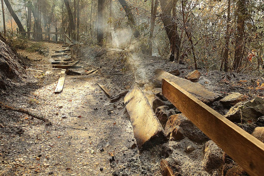 Wooden benches and railings smolder after the Jones Fire passed through the Independence Trail earlier this week.