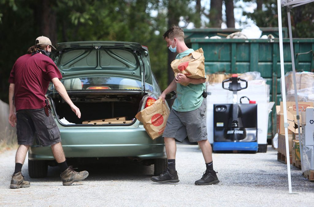 A pair of volunteers pack a trunk with food during Tuesday's drive-thru food distribution at the Oak Tree Campus on the San Juan Ridge. Distributions take place from 10 a.m. to noon on the second Tuesday of each month.