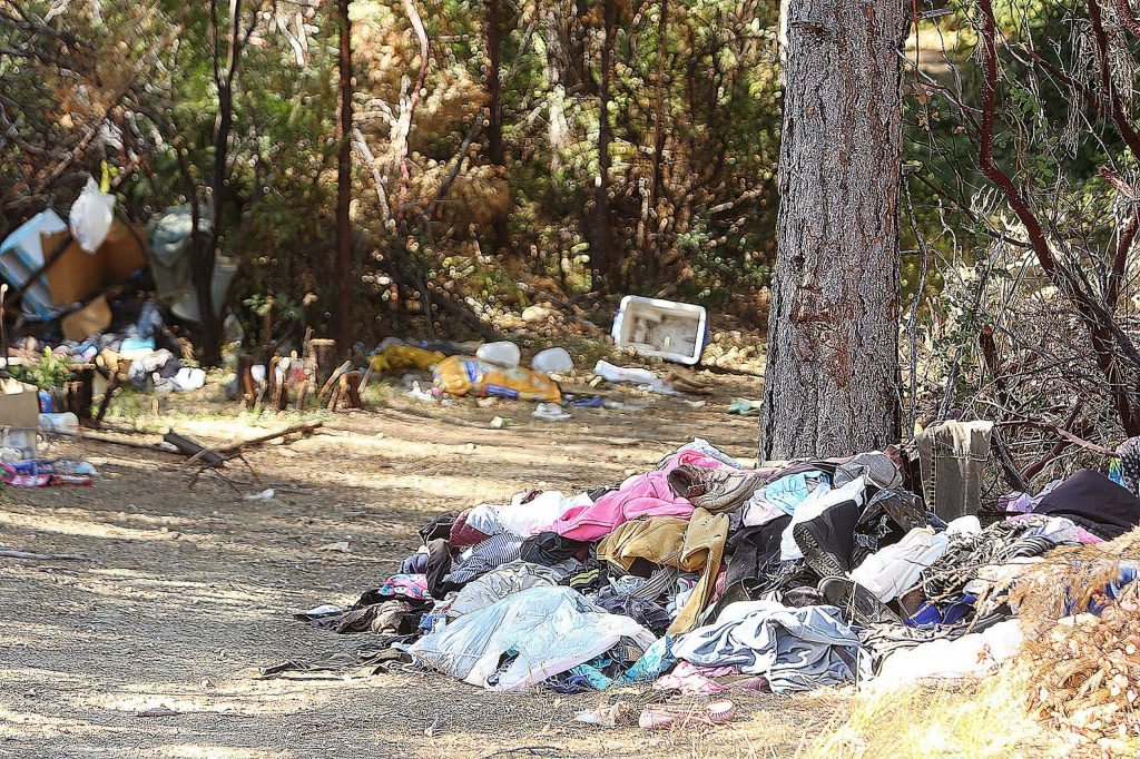 Piles of refuse left from an encampment now vacant for 3 months remain on land adjacent to Idaho Maryland and Brunswick Road. Grass Valley Police Department helps schedule camp cleanups after they have been vacated to ensure that illegal camping doesn't resume.
