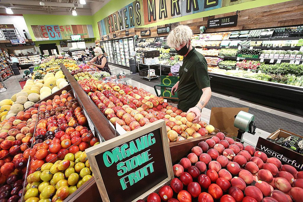 Assistant Produce Manager Liam Webb works to stock fresh produce at the new Holiday Market at Higgins Corner Friday during the first day of the new store being open.