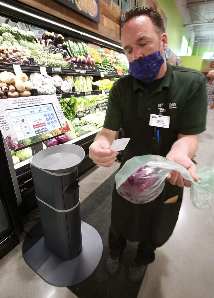 Holiday Market's Trevor Brady shows off the new scannable scales, which allow users to weigh and place a barcode on their produce to ensure less contact with people's food.