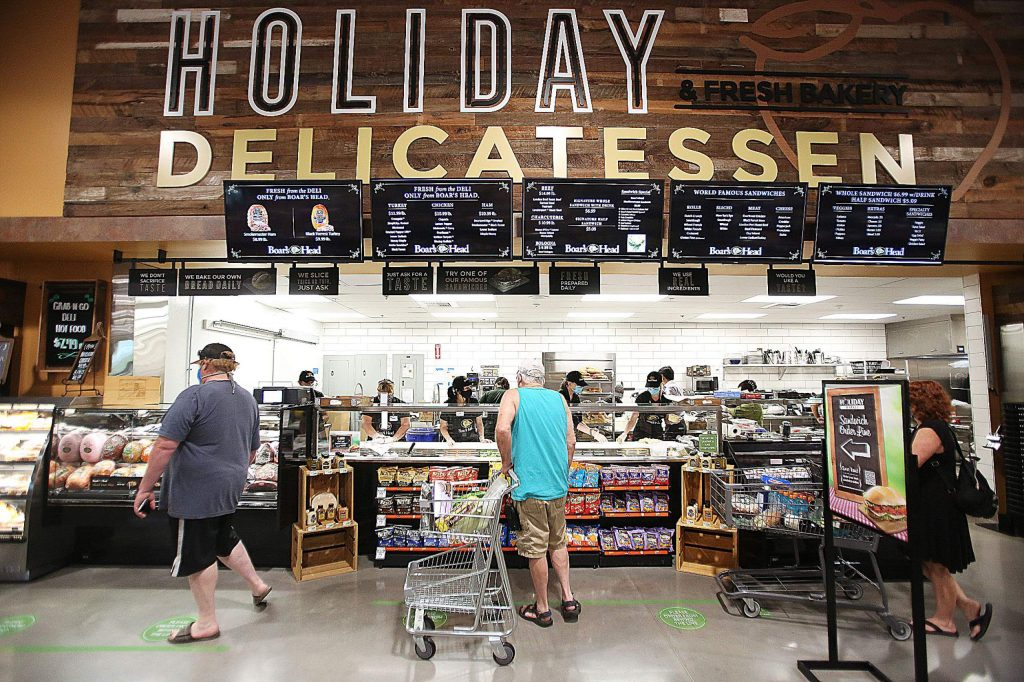 People order sandwiches from the new Holiday Market deli on Friday.