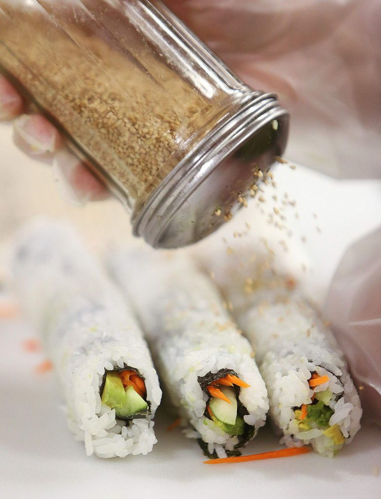 A vegetarian sushi roll is prepared fresh at the Higgins Corner Holiday Market deli during opening day Friday.