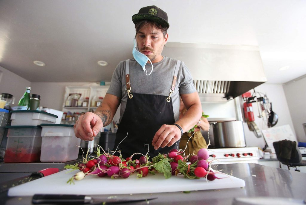 Noah Palmer of Osorio Kitchen in Grass Valley works on a dish with radishes from First Rain Farm last week from their kitchen.