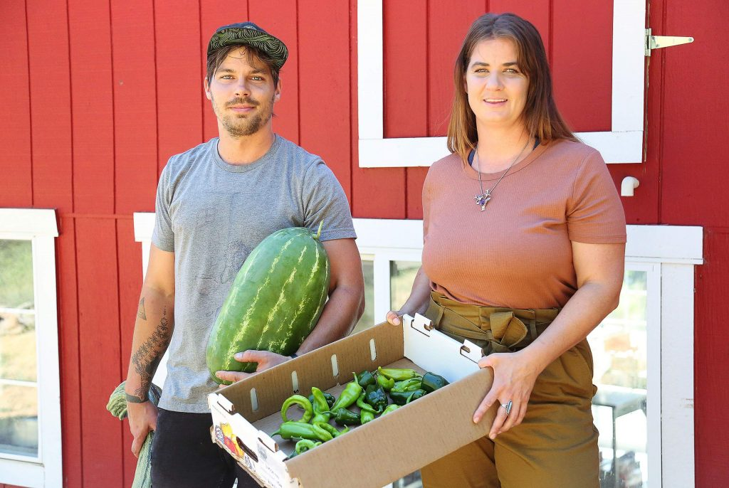 Noah Palmer and Megan Buser of Osorio Kitchen stand behind their Grass Valley business with some fruits and vegetables picked from their garden.