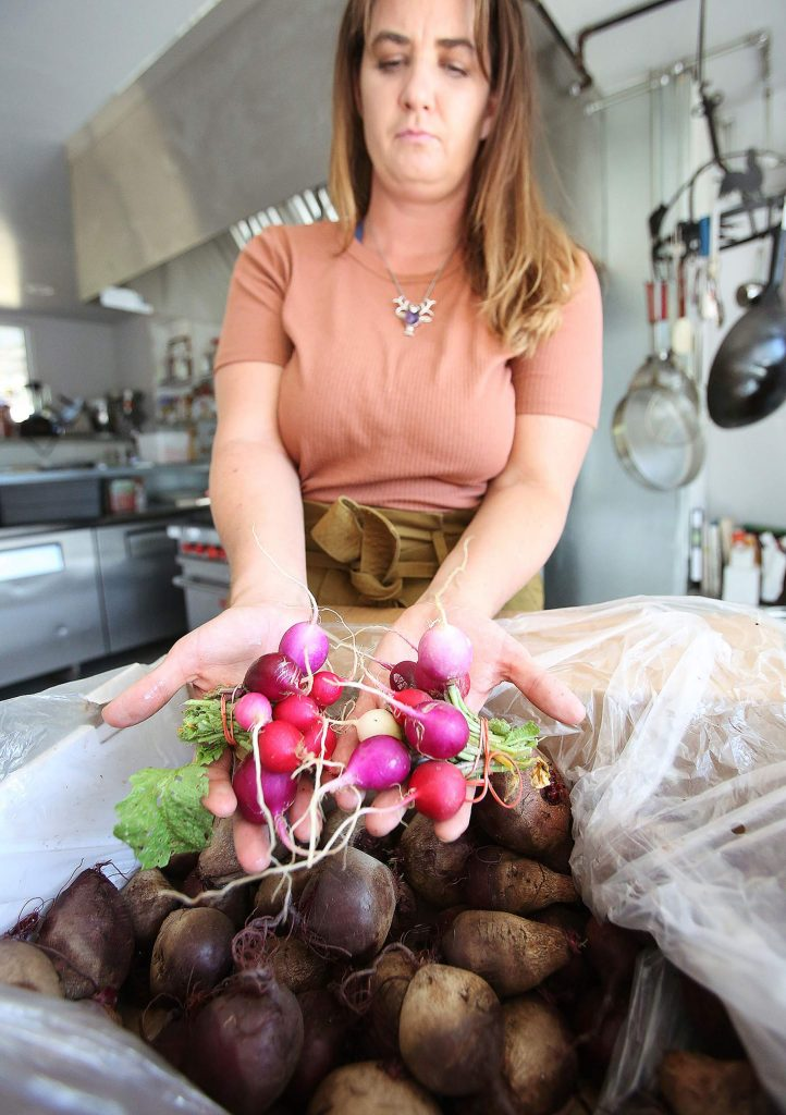 Osorio Kitchen's Megan Buser shows off some locally sourced radishes from First Rain Farms, and some beets from River Hill Farms.