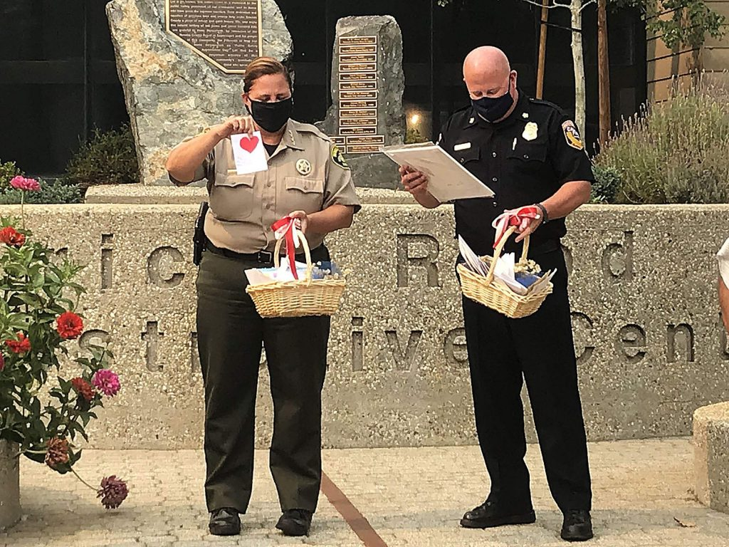 """Sheriff Shannan Moon, left, and Cal Fire Unit Chief Brian Estes received baskets of handwritten cards from Mt. St. Mary's Academy students. """"The Jones Fire frightens me, and yet you charge straight into it to put it out. Thank you and good luck,"""" read one of the cards, signed by an 11-year-old student named Clara."""