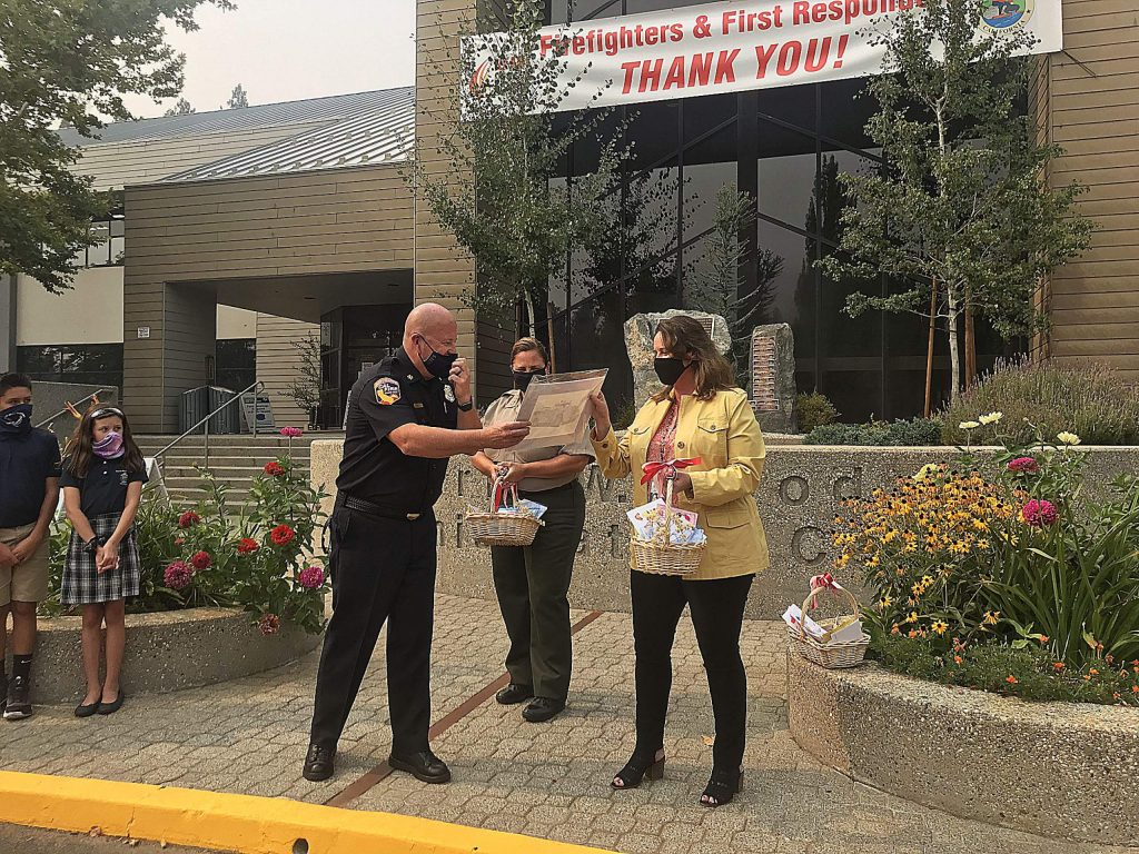 Cal Fire Unit Chief Brian Estes, left, presented Nevada County Executive Officer Alison Lehman with a fire engine illustration he drew, thanking Lehman and other county officials for their collaboration with first responders.