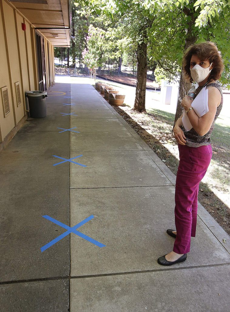 Deer Creek Elementary School principal Karen Mix shows off place markers on the ground where kindergarten students will be asked to stand while waiting to go into class.
