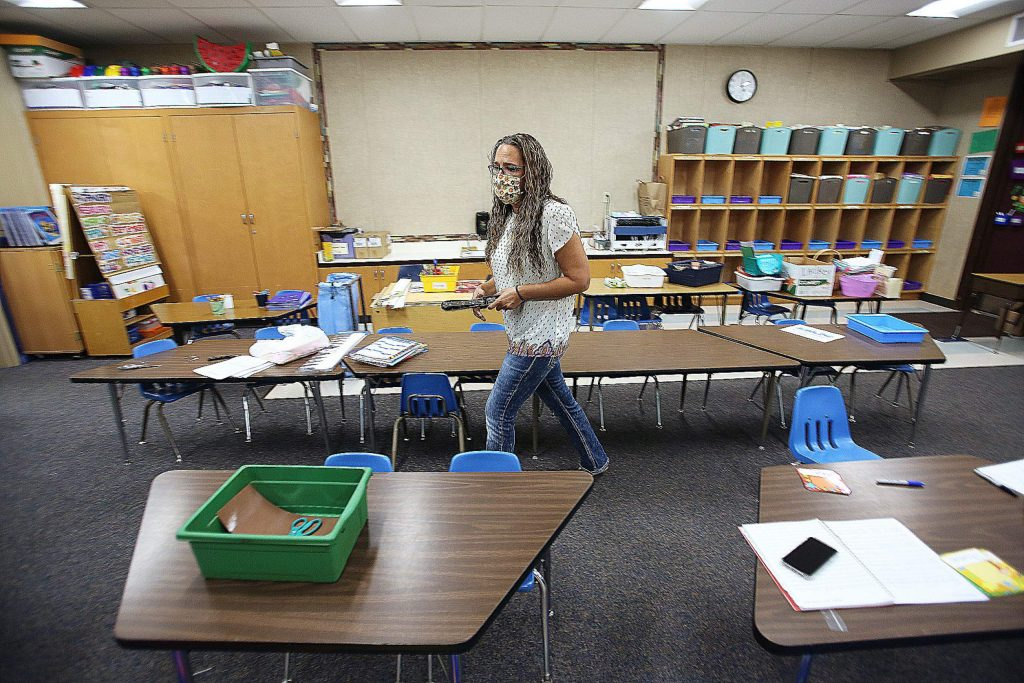 Deer Creek Elementary kindergarten teacher Vanessa Lackey walks through her classroom where her students' desks are placed apart in order to comply with social distancing in schools. Her class size is also being reduced.