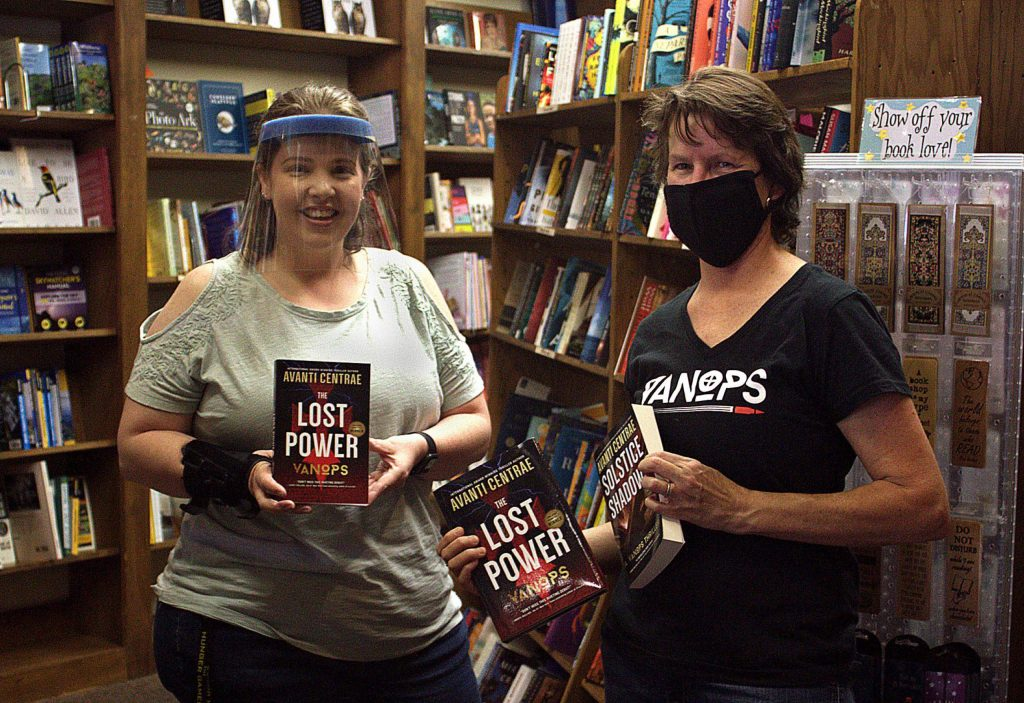 Wearing a clear, plastic face shield, Angie Kelsey (left) welcomed a visit from local author Avanti Centrae to The Book Seller in Grass Valley.
