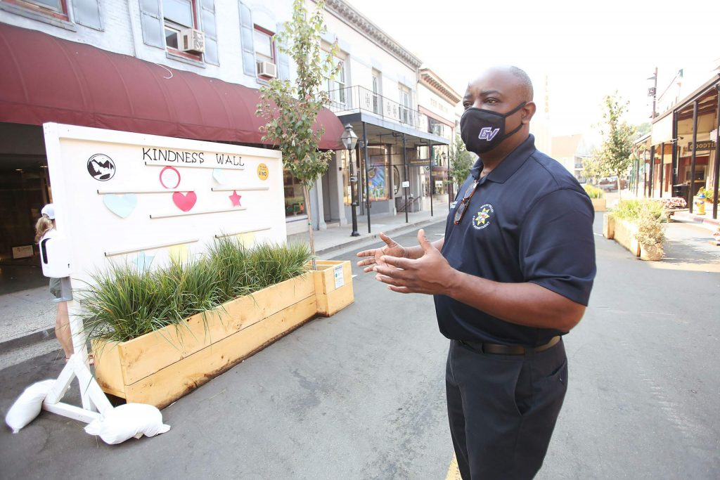 Jamal Walker stands next to the Kindness Wall placed along Mill Street for people to place their words of kindness and encouragement.