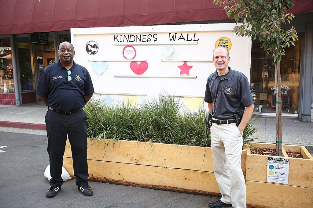 Community Relations Coordinator Jamal Walker and Police Chief Alex Gammelgard stand in front of the Kindness Wall placed along Mill Street in downtown Grass Valley.