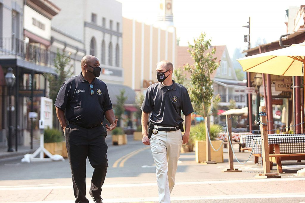 Community Relations Coordinator Jamal Walker takes a stroll down Mill Street with Police Chief Alex Gammelgard Friday morning. Walker has filled the new role created by the city.