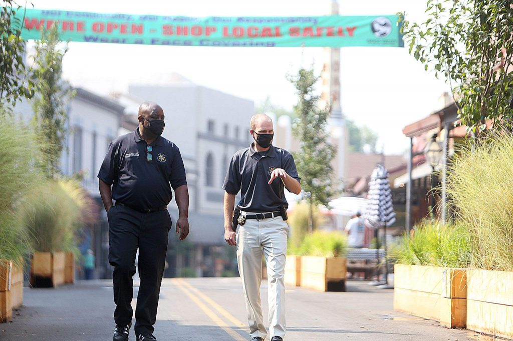 Community Relations Coordinator Jamal Walker and Police Chief Alex Gammelgard share a few words as they walk along Mill Street Friday morning.