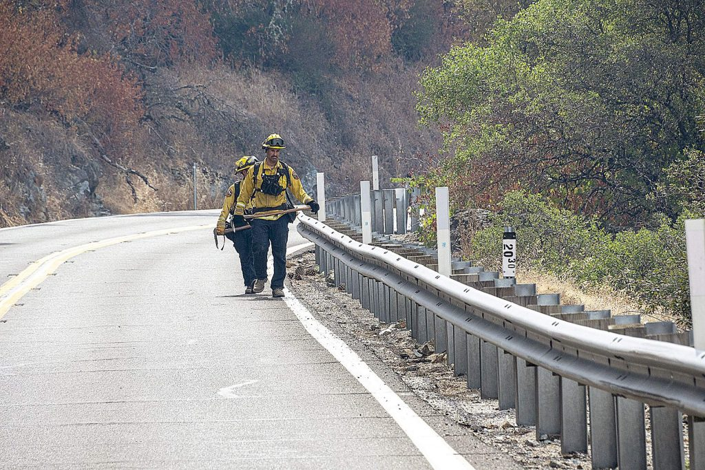 Two Cal Fire firefighters walk down Highway 49 Monday morning.