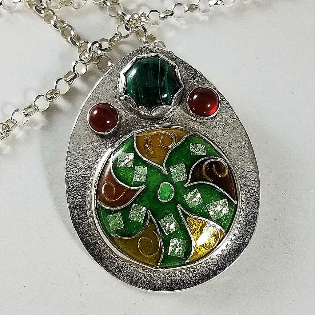 Vilina Hutter primarily uses silver, copper, colorful vitreous enamel and adds small gemstone cabochons to her pieces.