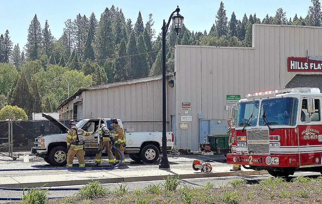 Grass Valley firefighters work quickly to douse the flames of a passenger vehicle fire that consumed the cab of a pickup along the 100 block of Idaho Maryland Road around noon Tuesday. A black plume of smoke was sent into the air and the nearby structure was briefly threatened before firefighters got a quick knockdown.