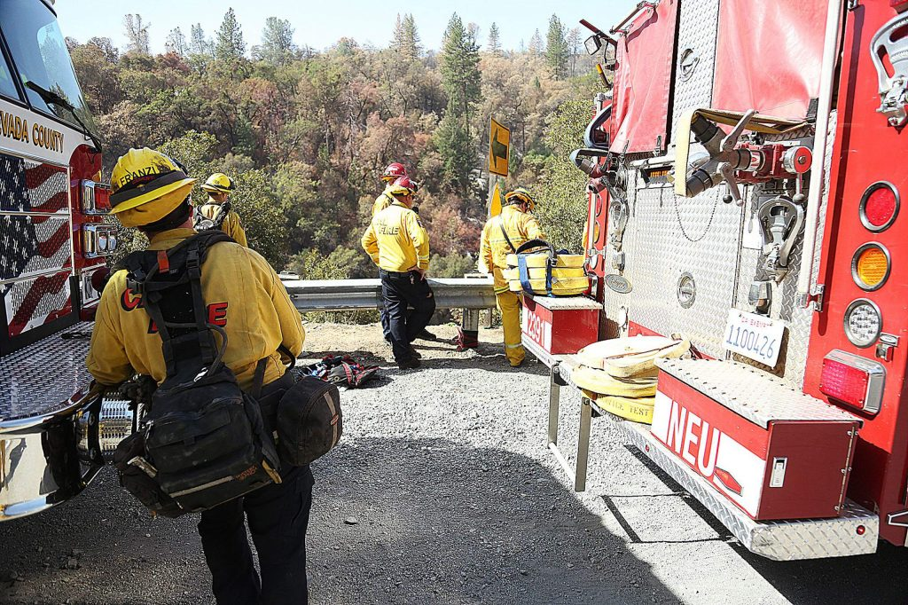 Cal Fire and Nevada County Consolidated firefighters prepare to use ropes to climb down a steep embankment along Highway 49 in the South Yuba River Canyon near Nishinam Gulch where a small flare up of the Jones Fire occurred Tuesday morning.