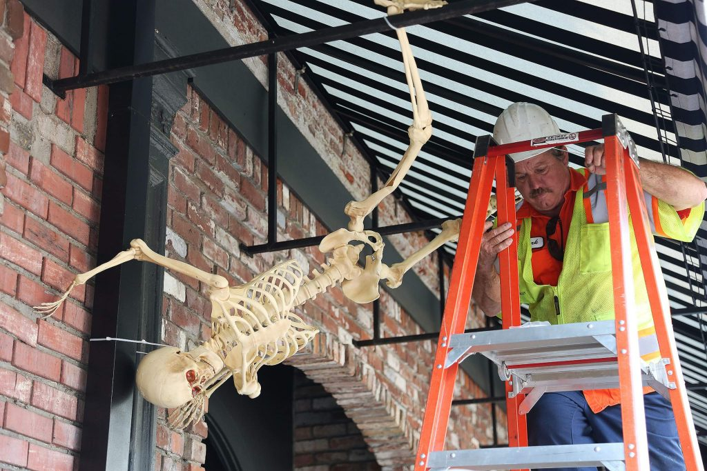Grass Valley Public Works employee Mark Kangas finishes placing a skeleton from the eaves of Watershed at the Owl Wednesday in downtown Grass Valley.