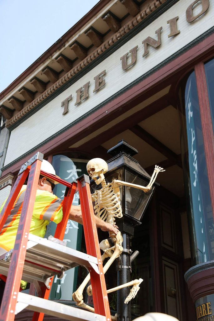 A city of Grass Valley worker places a skeleton on a lamppost in front of the historic home of The Union newspaper along Mill Street.