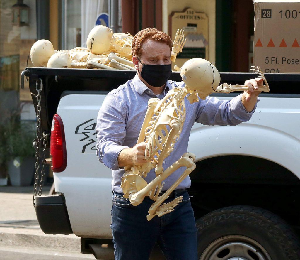 The Grass Valley city manager grabs a skeleton to be placed as decoration along Mill Street for the Halloween holiday.