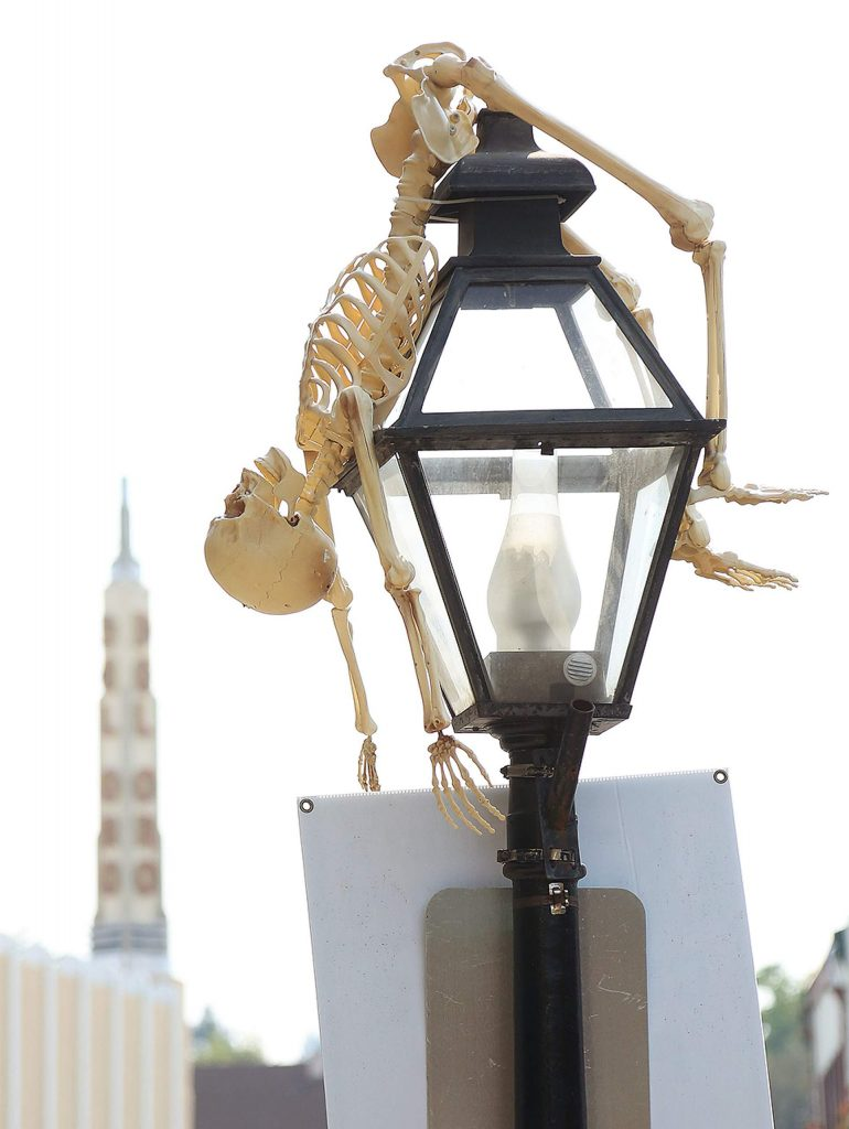A precariously placed skeleton sits spiked atop this streetlight near the Del Oro Theater.