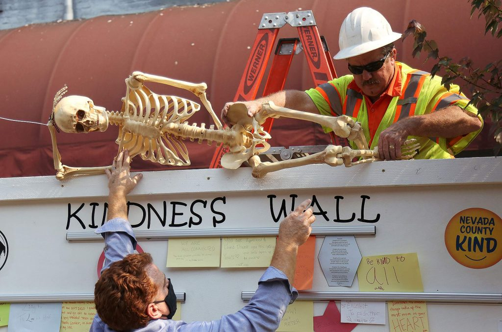 Grass Valley City Manager Tim Kiser and Public Works employee Mark Kangas work on placing a skeleton on the kindness wall along Mill Street in downtown Grass Valley's pedestrian access area.