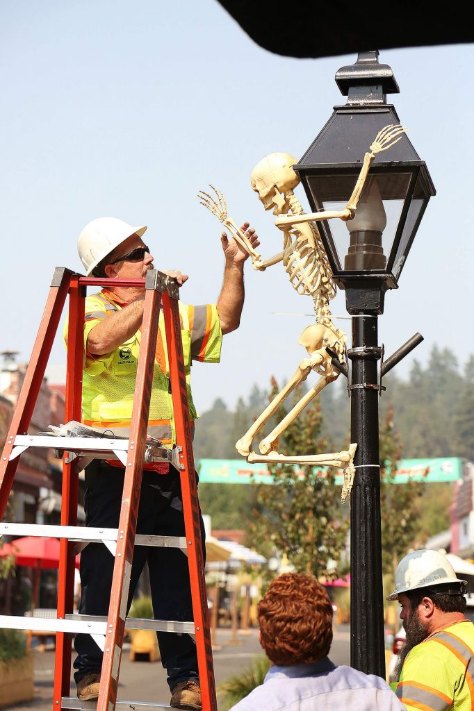 City of Grass Valley employees place a Halloween decoration along Mill Street Wednesday afternoon.