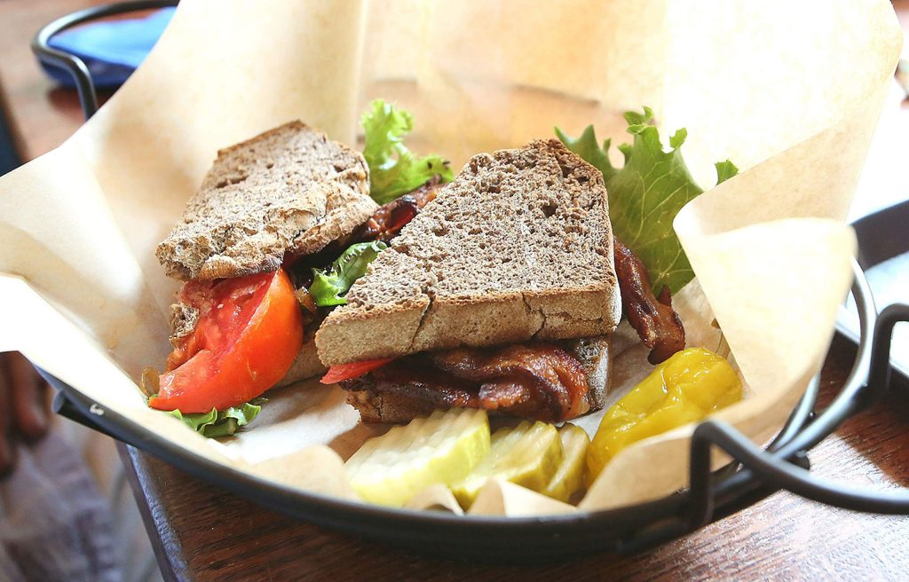 A customer shows off the Creole BLT with applewood smoked bacon last week at Ike's Quarter Cafe on its first day of reopening.