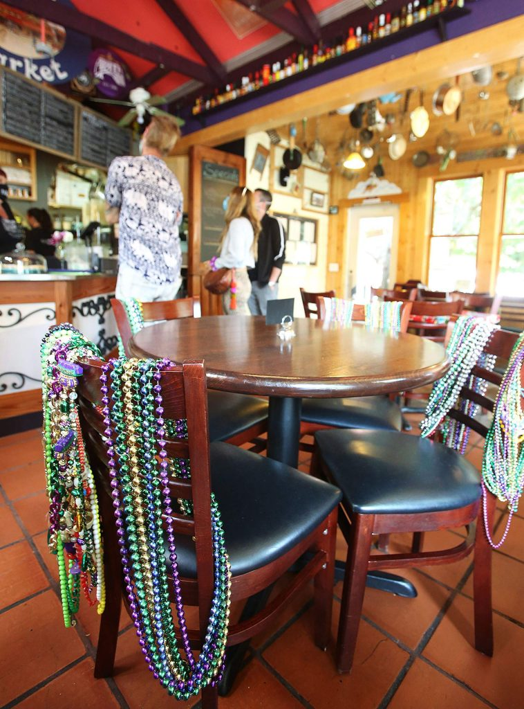 Mardi Gras beads double as festive decorations and seat holders at Ike's Quarter Cafe in Nevada City, where a percentage of indoor dining has been allowed again.