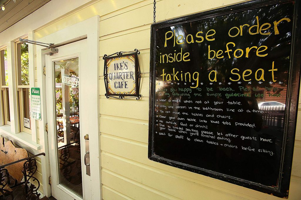 Signage outside of Ike's Quarter Cafe asks customers to order inside before taking a seat.