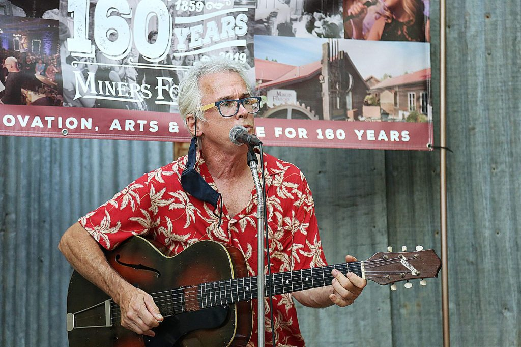 Nevada City musician Peter Wilson provides live music outside of the Miners Foundry for a group of people Saturday evening off Spring Street in downtown Nevada City, where more establishments are moving their operations outdoors.