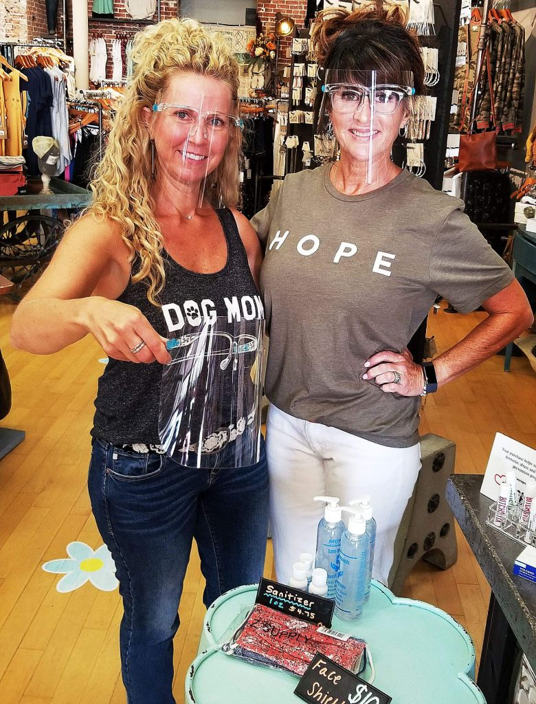 LaTeDa owner Becky Ingram (left) and sales manager Jennifer Cantrell model face shields for sale at the Mill Street store.