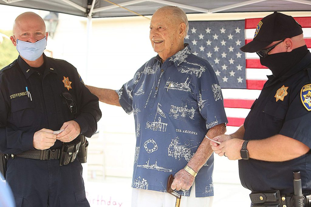 Grass Valley CHP Commander George Steffenson (left) and CHP PIO Mike Steele are given a challenge coin from Lou Conter after helping to organize Saturday's surprise drive-by birthday salute in front of his Grass Valley home. Conter turned 99 Sunday.